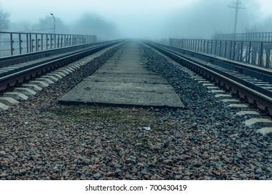 Walking in the fog.   rail road tracks , the prospect forward .