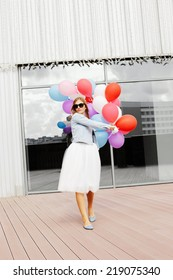 Walking girl with colorful balloons in one hand. Wearing sunglasses. City view. Outside.