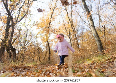 walking girl with toy in hand in forest