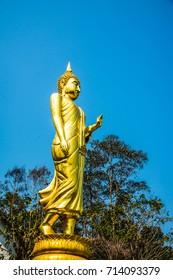 Walking golden buddha statue at Phra That Khao Noi temple, Thailand.