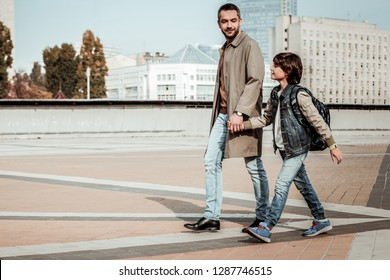 Walking hand in hand with a kid. A father walking with his son outdoor