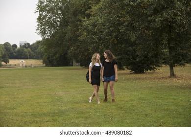 Walking Hand in Hand. Two young women are walking through the park hand in hand as they chat together.