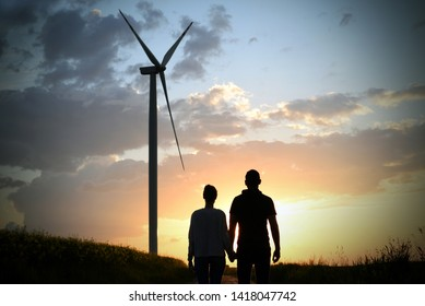 walking lovers, couple in sunset light, windmill in the background