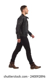 Walking man in black leather jacket and black jeans. Full length studio shot isolated on white.