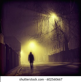 The walking man's silhouette in night fog at artificial light