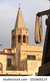 Walking the Medieval City Walls of old Alghero town named Cristoforo Colombo.  Among the roofs of the characteristic houses stands the bell tower of the Cathedral of Santa Maria. Sardinia, Italy
