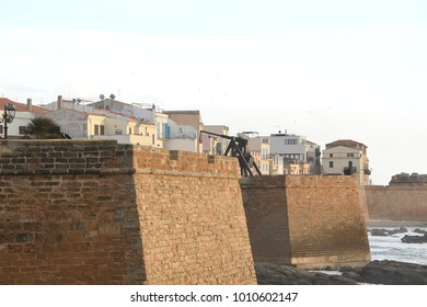 Walking the Medieval City Walls of old Alghero town named Cristoforo Colombo.  Among the roofs of the characteristic houses stands the bell tower of the Cathedral of Santa Maria. Sardinia, Italy.