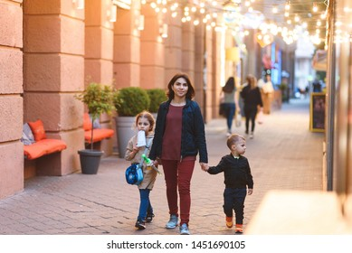 walking mother with two children at evening street