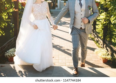 walking newlyweds holding hands at yard