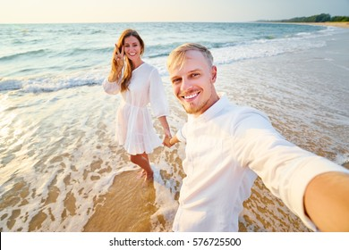 Walking on the sea shore. Pretty young loving couple taking selfie together on smartphone on beach.