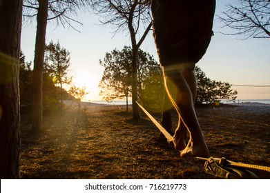 Walking on slackline in front of the sea in backlight