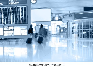 Walking passengers with baggage in airport terminal. Blur motion
