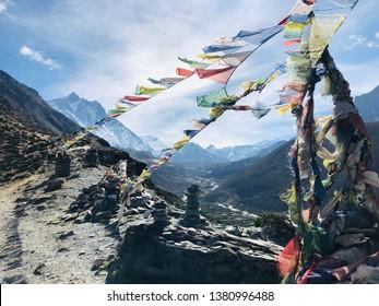 Walking past streams of prayer flags in Nepal.