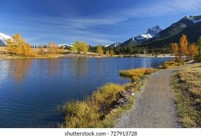 Walking Path around Quarry Lake and Distant Mountain Tops Landscape above Town of Canmore in Foothills of Canadian Rocky Mountains near Banff National Park