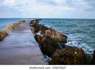 Walking path leading into the ocean a jetti along the gulf coast extends far into the horizon near corpus christi texas