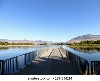 A walking path looking out towards the North Thompson River, in Kamloops, British Columbia, Canada.  Beautiful reflection of the clouds, sky, and mountain in the river.