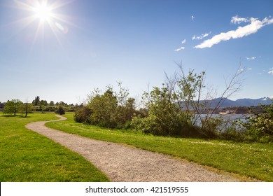 A walking path in a ocean-side city park on a sunny day.