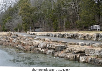 A walking path with a park bench and stone wall adjacent to the shore of a frozen pond.
