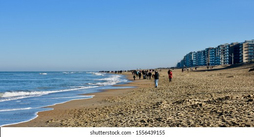 walking people along the Belgian coast on a sunny winter Sunday afternoon between Koksijde and De Panne