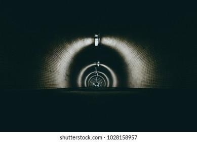 Walking People silhouette in dark urban tunnel . People walking to the light in dark tunnel .