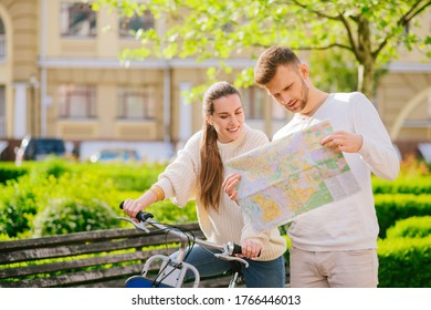 Walking route. Smiling young woman sitting on bicycle and focused man with map in his hands standing nearby, studying