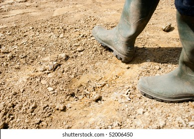 Walking with rubber boots on dry earth