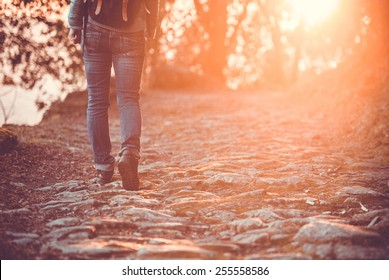 Walking or running legs, adventure and exercising in mountains on rocky road at sunset. Toned picture