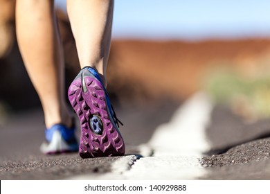 Walking or running legs on mountain road, adventure and exercising in summer nature. Female hiker or runner foot and sport shoes doing workout outdoors.