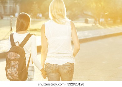 Walking side by side. Horizontal shot from behind of mother walking her teen daughter with a backpack to school holding hands