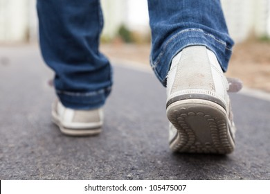 Walking in sport shoes on pavement in park