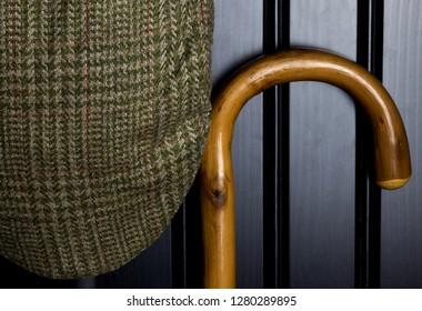 Walking stick and tweed cap hanging on black cupboard door
