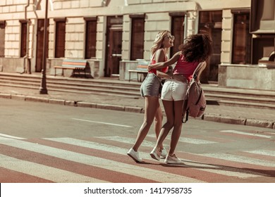 Walking the streets with friends. Dazzling blonde long-haired smiling radiant pleasing nice-looking young lady hugging with her good-appealing Afro-American girlfriend while walking the streets.