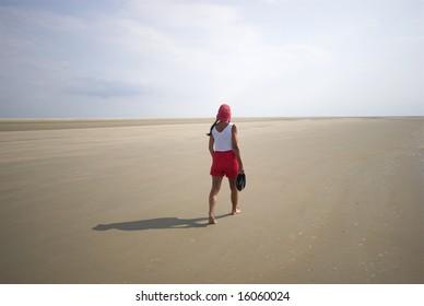 Walking in the Sun. Woman walking on Koresand,  Low Tide Island in Denmark