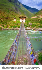 Walking suspension bridge over the river with colorful prayer flags in Bhutan