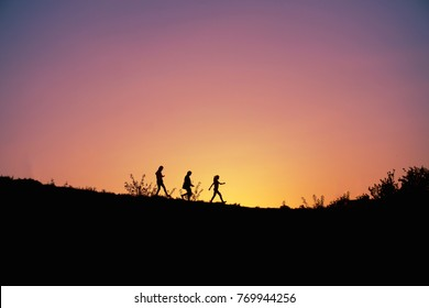 Walking three young people silhouettes on pink yellow violet purple lilac sunset time today