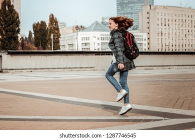 Walking through the city center. A girl happily skipping through the city center