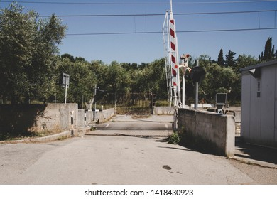 Walking through the countryside of Puglia, in southern Italy. A small road leads to an old level crossing that divides the city from the countryside.