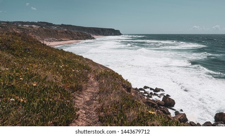 Walking track along cliff tops with view of the Atlantic ocean and waves, taken in a sunny summer day in Praia das Maçãs, Colares, Portugal, with view of Praia Grande