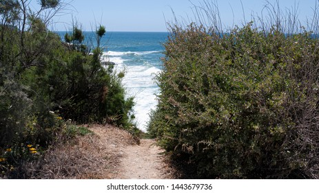 Walking track along cliff tops with view of the Atlantic ocean and waves, taken in a sunny summer day in Praia das Maçãs, Colares, Portugal.