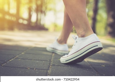 Walking. Woman walking around in the park in canvas shoes