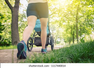 Walking woman with baby stroller enjoying summer day in park. Jogging or power walking supermom, active family with baby jogger.