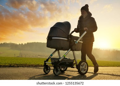 Walking woman with baby stroller at sunset.