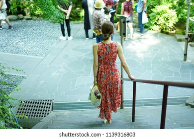 A walking woman in a garden of temple.