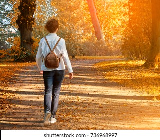 Walking woman on a fall day in the beautiful autumn park
