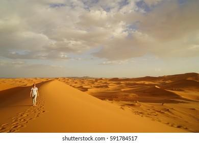 Walking woman in Sahara Desert, Merzuga, Morocco, Africa