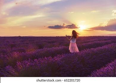 Walking women in the field of lavender.Romantic women in lavender fields, having vacations in Provence, France.A girl in white dress walking trough lavender fields at sunset.