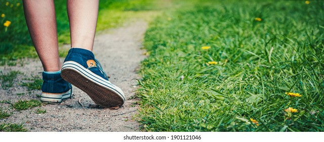 Walking women leg in jeans sneaker shoes on the road and green grass