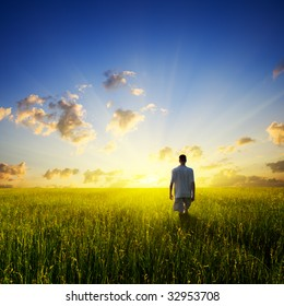 walking young man over field and sunset