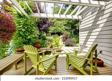 Walkout deck with attached pergola. Rest outdoor area with two chairs and benches