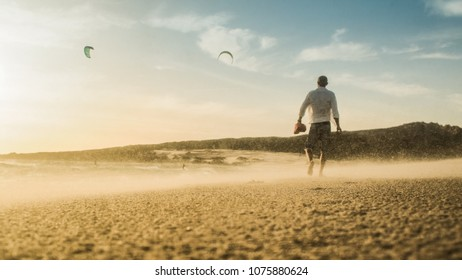 walkting hipster MAN with tattoos and beard from the back on a sandy and windy beach in spain